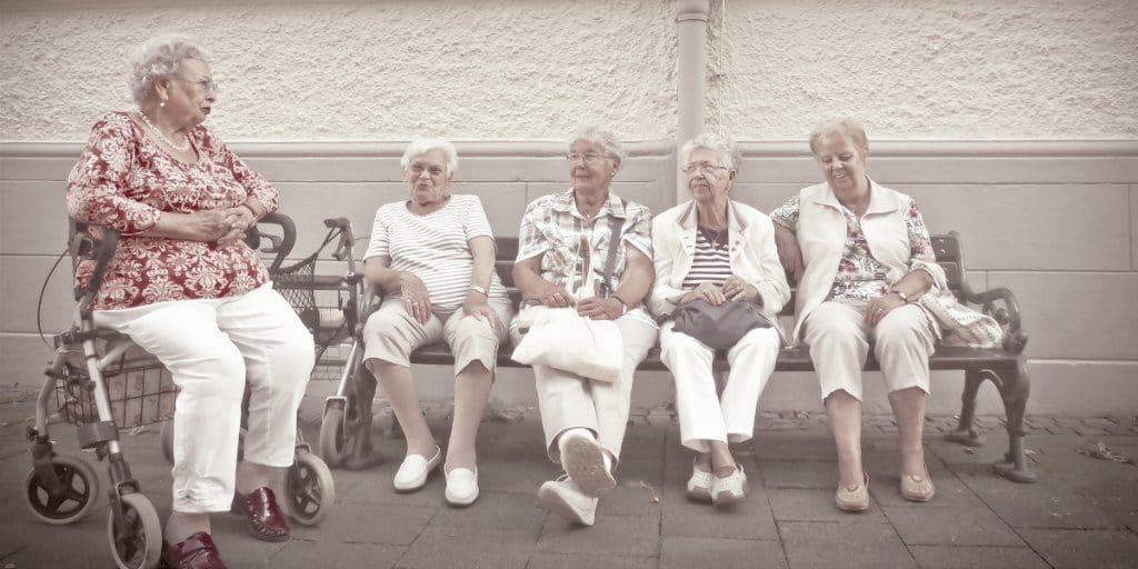 5 Grannies sitting on a bench in front of a building