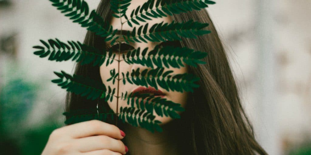 dark haired women holding a fern leaf in front of her face as she peaks through leaves