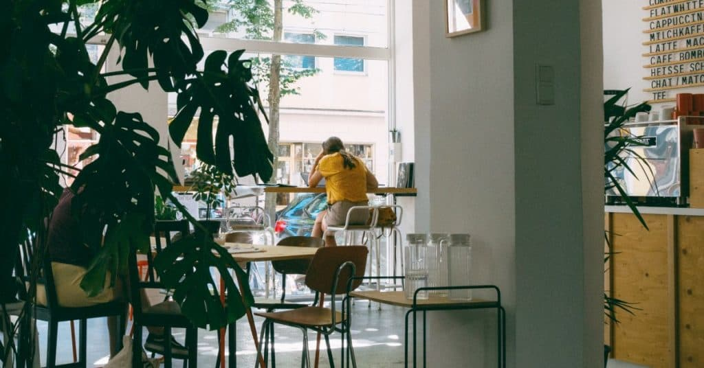 woman sitting in a cafe looking out the window