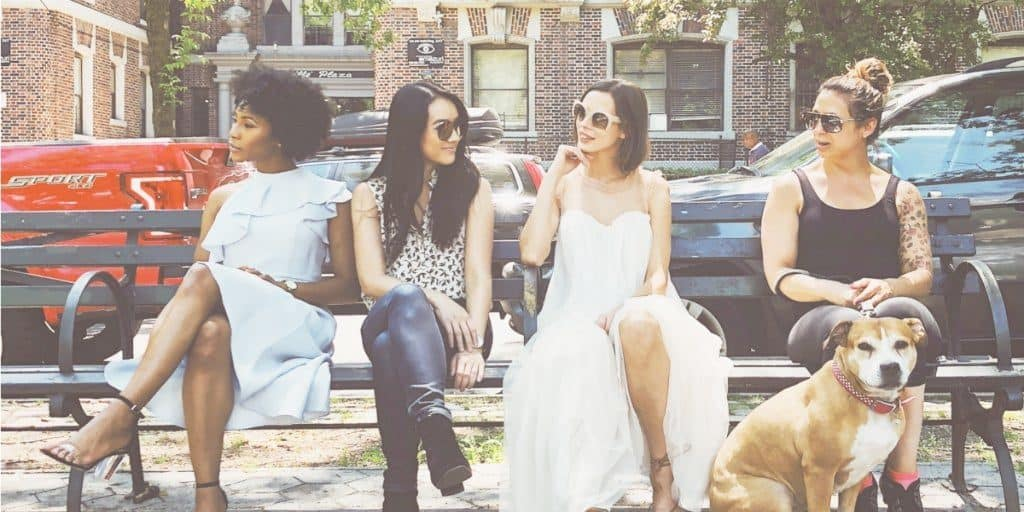 four women sitting on a bench in the city