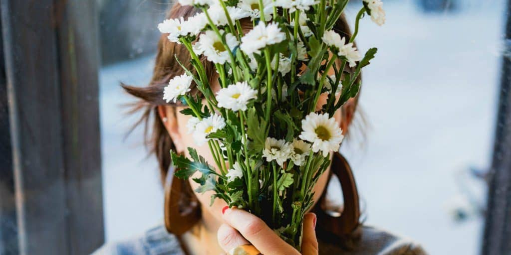 women holding a bunch of white daisies in front of her face