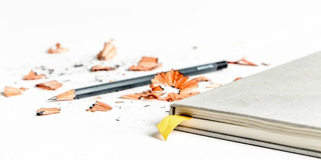 a book, pencil, and pencil shavings on a white background