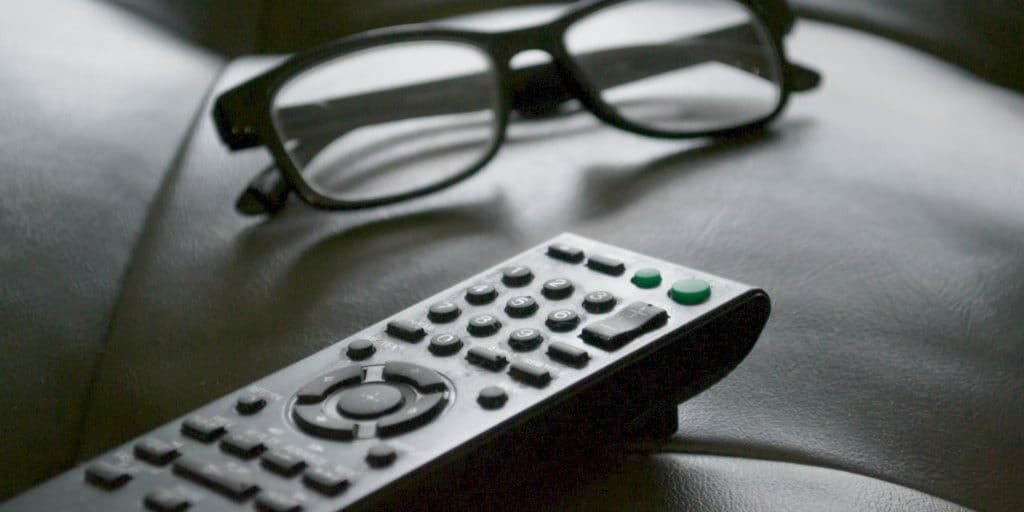 TV remote control and glasses on a leather couch