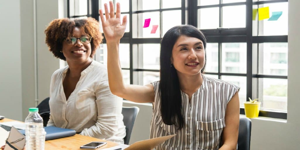 woman-raising-her-hand-with-confidence-in-meeting