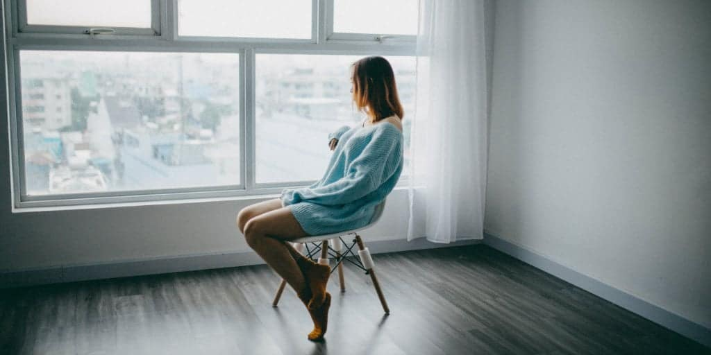female sitting in a chair in an empty apartment