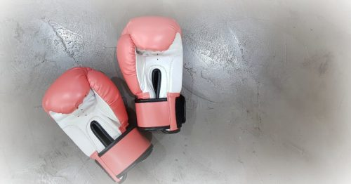 pink and white boxing gloves on cement background