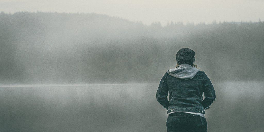 women looking out at the fog of a lake