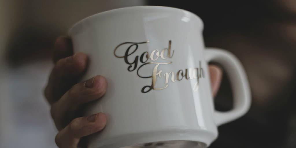 white mug with the words good enough in gold letters