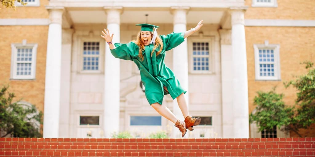 female celebrating college graduation by jumping in the air and kicking her heels