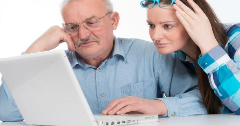 women helping elderly father with computer looking concerned